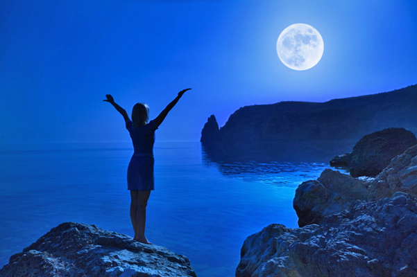 Photo of woman with arms up and open to the moon