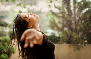 A woman in worship while standing under the rain