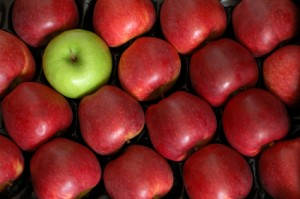 One green Granny Smith in a box of Red Delicious apples
